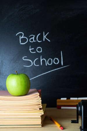 school teachers: Maestro de escritorio con un mont�n de libros, una manzana y otros equipos. De Regreso a la Escuela 'Las palabras escritas con tiza en la pizarra en el fondo de enfoque suave. Foto de archivo