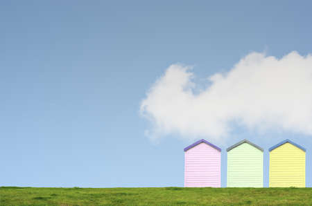 A row of three colourful beach huts on top of a grassy hill against a bright blue sky with white fluffy cloud. Copy space above and left. photo