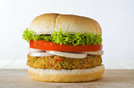 A cheese-free vegetarian burger made from vegetables and breadcrumbs, stacked with onion rings, slice of tomato and curly lettuce, in a bap on a wooden board. Banque d'images