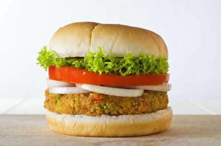 verduras: Un queso sin hamburguesa vegetariana a base de verduras y pan rallado, apilado con aros de cebolla, rebanada de tomate y lechuga rizada, en un bautismo en una tabla de madera. Foto de archivo