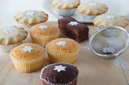 sifter: A group of Christmas cakes and mince pies, decorated with star shapes from sifted icing sugar, on a wooden chopping board with plate in background, and sifter with scattered icing sugar to the right.  Stock Photo