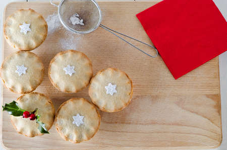 personalised: Overhead shot of mince pies decorated with holly sprig and sifted icing sugar in star shapes.  An old tea straining sieve sits on wooden board with sprinkled icing sugar. Red napkin on upper right.