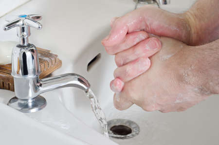 Male hands being washed in old china sink with water running from stainless steel tap, and a bar of soap resting on a wooden soap dish. photo
