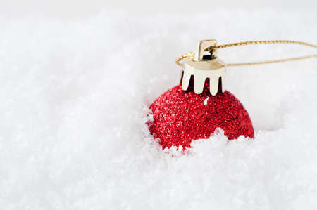 sunk: A sparkly red glitter Christmas bauble, with gold clasp and gilt string, sunk into fake white snow to the right of frame.  Snow provides copy space to left. Stock Photo