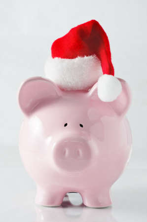 A piggy bank wearing a santa hat to signify saving money to plan ahead for the cost of Christmas. photo