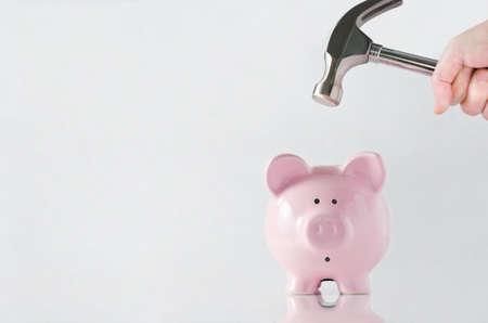 Eine Hand, die einen Hammer, der über einem rosa china Sparschwein angehoben wird, mit einem schockiert und besorgt Gesichtsausdruck reflektierende Oberfläche und hellgrauem Hintergrund Copy space auf der linken Seite Standard-Bild - 16028338