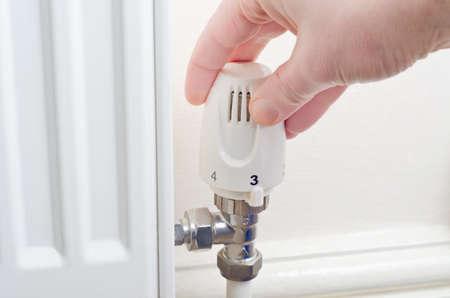 guarniciones: Primer plano de una mano girando una perilla radiador ya sea hacia arriba o hacia abajo. Accesorios de acero y parte del radiador visible, con la pared pintada de crema y z�calo en el fondo.