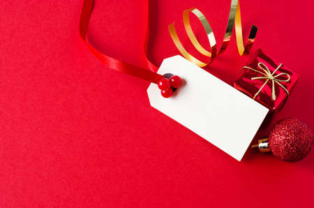 christmas tag: A blank Christmas gift tag, decorated with red ribbon and artifical holly berries, on a matte red background with shiny small gift box, glittery bauble, and gold foil spiral.  Copy space on tag and to its left. Stock Photo