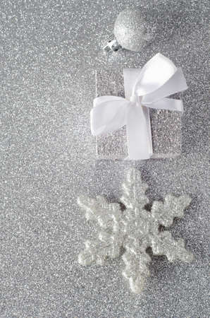 overhead shot: Overhead shot of three silver glittering Christmas ornaments on a silver glitter background. Includes a bauble, a Christmas gift with white ribbon bow, and a star shaped snowflake.  Copy space to left. Stock Photo