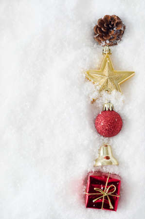 An uneven vertical line of Christmas ornaments running from top to bottom of frame, half buried in snow, on right hand side.  Copy space to left. photo
