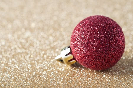 A single, sparkly red bauble, coated in glitter, resting on a gold glitter background that softens into soft focus bokeh in the background.  Copy space to left.