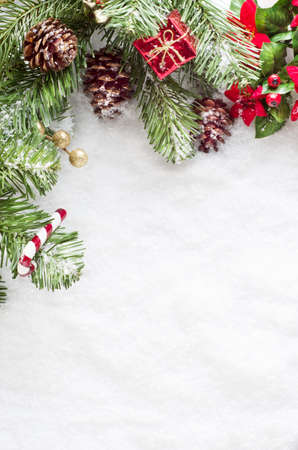 A Christmas border to left and top of frame consisting of artificial foliage, real pine cones and decorative ornments, sprinkled with snow on a fake snow background.   Snow provides copy space.