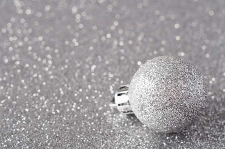 A single silver bauble, coated in glitter, resting on a silver glitter surface that softens into bokeh in the background.