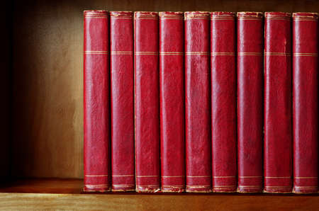 with spines: A row of old, battered, matching encyclopaedias (circa 1950s) lined up on a shelf, with titles removed to leave blank spines.  Red leather effect with gold striped trims.  Shelf has been darkened artificially to give impression of age. Stock Photo