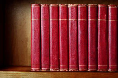 Eine Reihe von alten, ramponierten, passend Lexika (circa 1950) aufgereiht auf einem Regal, mit Titeln entfernt leere Stacheln verlassen. Red Lederoptik mit Gold gestreiften trimmt. Shelf wurde künstlich, um den Eindruck des Alters geben verdunkelt.