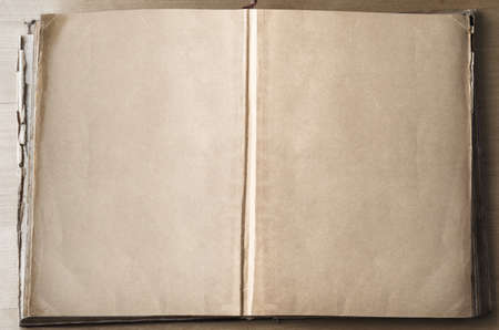furled: An old vintage book on a wooden table, opened out from its centre to expose blank, parchment coloured pages.