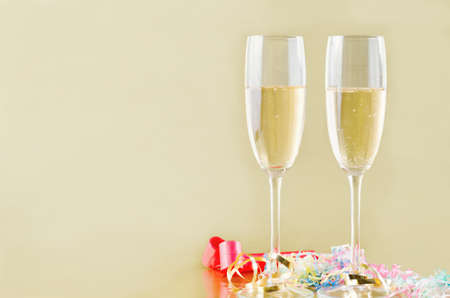 blowers: Two fluted champagne glasses with bubbles rising on a gold background with popper streamers and party horn blowers on the surface below.  Copy space to the left.