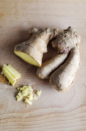 overhead shot: Overhead shot of whole, sliced and roughly chopped ginger root on an old, used  wooden chopping board with many knife cuts on its surface.