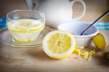 lemon water: Kitchen preparation scene containing ingredients for a honey, lemon and ginger drink - a herbal home remedy for colds.