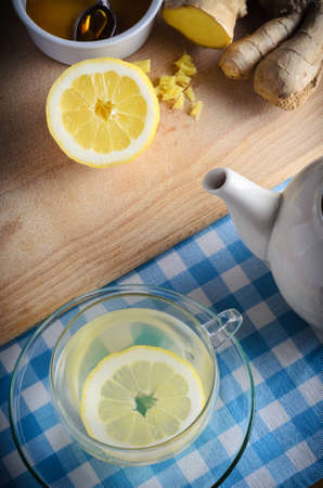 cold remedy: Vertical kitchen preparation scene containing ingredients for a honey, lemon and ginger drink - a herbal home remedy for the cold and flu season.