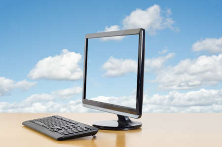 signify: A computer monitor and keyboard on a shiny wooden desk, angled and facing left, with a bright, light blue sky in the background with passing white fluffy clouds, also displayed in screen to signify cloud computing. Stock Photo