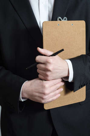 Close up crop shot of a male (torso) in a dark suit and white shirt, holding a clipboard and pen, waiting to collect research data or to confirm a booking or check his list.