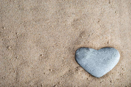 nestled: A grey heart shaped stone nestled in golden sand at bottom right of frame.  Copy space in sand. Stock Photo