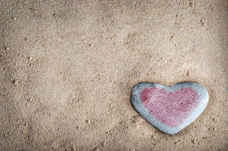 heart of stone: A grey heart shaped stone on grainy sand, tinted with a red heart.  This version is vignetted and edited to give a retro or lo-fi appearance. Stock Photo