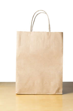 An unbranded brown paper carrier bag with twisted handles on a light wood table with white background, facing front with empty space for text. Stock Photo - 18244316