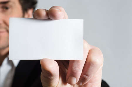 A man in a black suit with white shirt holding up a blank business card to display to viewer. photo
