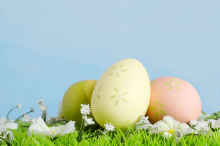simulate: Eggs decoratively painted on artificial grass with fabric flowers photographed against a painted blue background to simulate Spring sky.