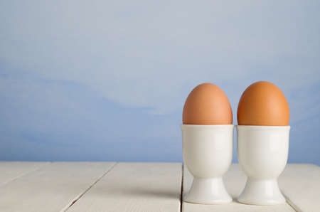 Two fresh brown undecorated eggs, side by side in white porcelain egg cups against a painted blue sky effect background Stock Photo