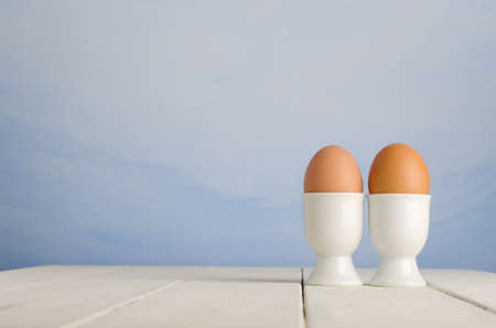 Two fresh brown eggs in egg cups on an old, cream painted wood plank farmhouse table, with painted blue sky effect background. photo