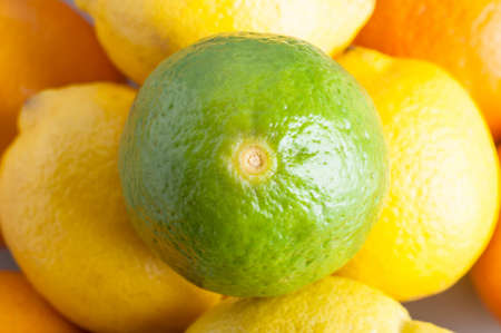 zesty: Close up (macro) overhead shot of a lime, sitting on top of a round of lemons, beneath which are oranges.  Represents citrus fruits containing Vitamin C.  Landscape orientation.