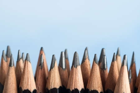 upright row: An uneven row of mixed graphite pencils, standing upright against a sky blue background with their tips pointing upwards from the bottom half of the frame.