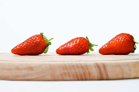 intact: A line of three red strawberries with leaves and short stalks intact.