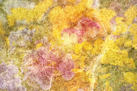 hues: Abstract background texture of a piece of stone, scattered with smaller stones and overlaid with bright yellow, pink and green hues.