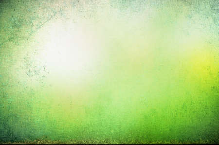 scuffed: Abstract grungy bordered background texture with appearance of glowing yellow sunlight in a misty green forest glade.