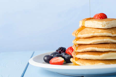 pancakes: A stack of breakfast pancakes topped with a strawberry. Stock Photo