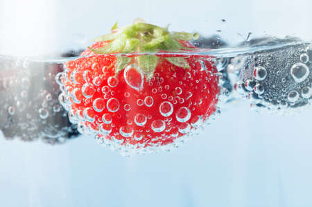 Close up (macro) of a bright red fresh strawberry, floating in sparkling water and covered in oxygen bubbles. photo