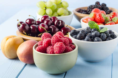 cherry varieties: A selection of different Summer fruits, in a variety of bowls on a painted blue wood planked farmhouse kitchen table, against a light blue background.