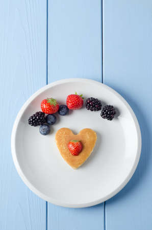 vertical orientation: Overhead shot of a heart shaped breakfast pancake underneath an arc of Summer fruits and topped with a cut strawberry.  Food set on a white china plate with a painted wood planked table underneath.