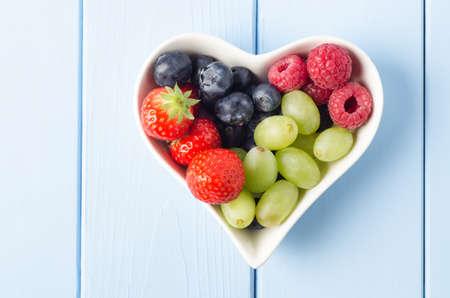 dieta sana: Overhead shot de una selecci�n de frutas en un taz�n en forma de coraz�n, en una madera de color azul claro tablones superficie.