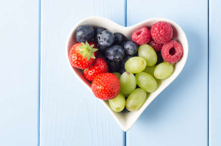 healthy snacks: Overhead shot of a selection of fruits in a heart shaped bowl, on a light blue wood planked surface. Stock Photo