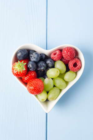 Vertical overhead shot of a selection of fruits in a heart shaped bowl, on a light blue wood planked surface. Imagens