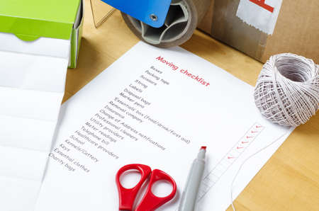 A house moving checklist on a table, surrounded by labels, packaging tape roller, scissors, red marker pen, a ball of string and a sealed box.  Some of the checkboxes have been ticked in red.
