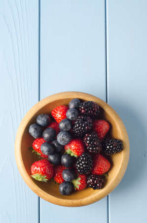 Overhead shot of a round wooden bowl containing berry fruits on a painted pale blue wood planked table. Subject placed in lower half of frame with planking providing empty space above. photo