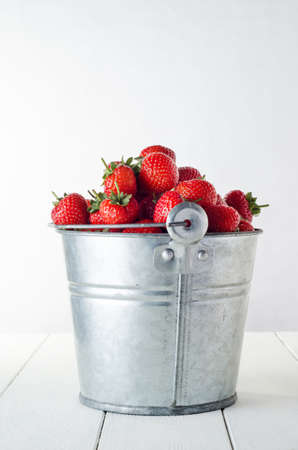 side table: Side view of an old, pitted and scratched aluminium metal bucket filled to overflowing with harvested red strawberries on a white painted wood planked table.