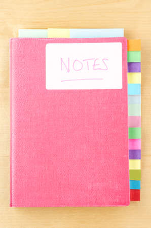sectioned: Pink notebook on a light wood background.