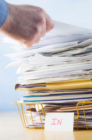 Business image of a male hand with blue shirt cuff visible, adding or removing document from tall pile in overflowing office In tray. Stock Photo - 21547373